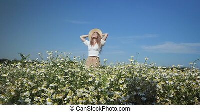 Woman dancing in a field of chamomiles