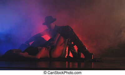 Woman dancing in colored smoke. Man with a hat is looking at her