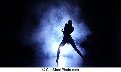 Woman dancing in studio, silhouette. Dark background, blue...