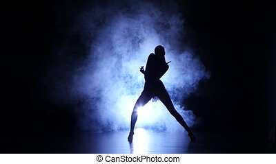 Woman dancing in studio, silhouette. Dark background, blue backlight