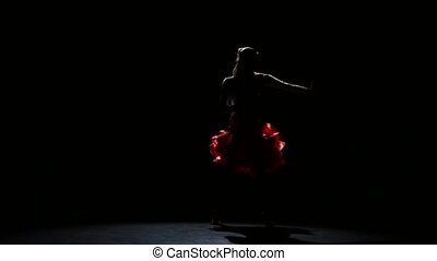Woman dancing latin in a studio on a dark background, a silhouette