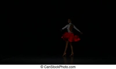 Woman dancing latin in a studio on a dark background