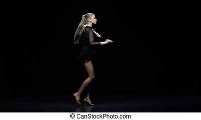 Woman dancing latina in the studio, black background. Slow motion
