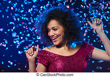 Woman dancing on a party over colorful background with...