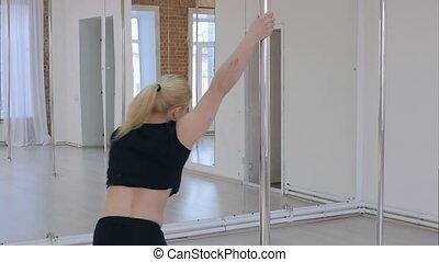 Woman dancing on pylon in studio