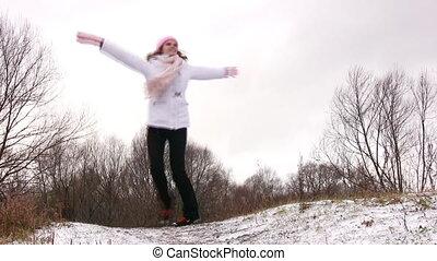 Woman dancing rotating on snow meadow.