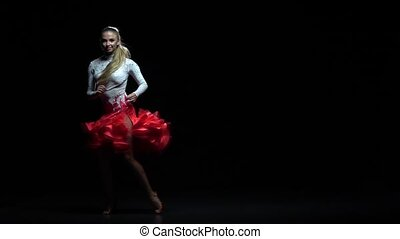 Woman dancing rumba dance, dark background. Slow motion