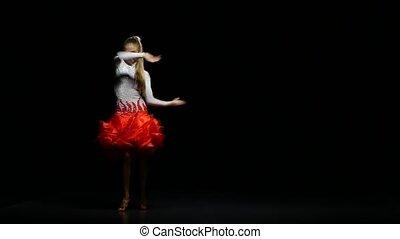 Woman dancing rumba in a studio on a dark background