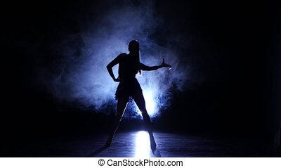 Woman dancing rumba in studio, silhouette. Dark background, blue backlight