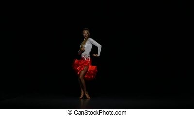 Woman dancing samba in a studio on a dark background