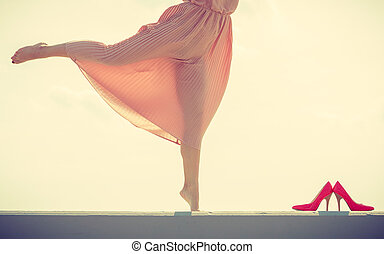Woman dancing wearing long light pink dress