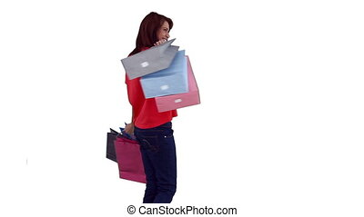 Woman dancing while holding several shopping bags