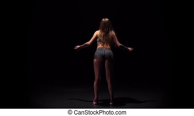Woman dancing with back to the viewer. Slow motion