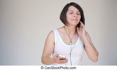 Woman dancing with earbuds listening to music on mobile...