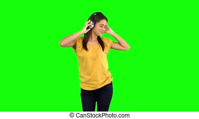 Woman dancing with headphones on gr