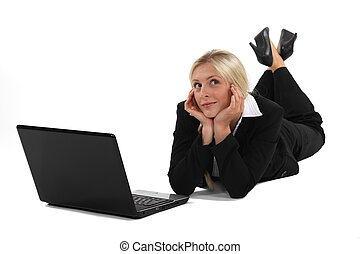 Woman daydreaming in front of her laptop