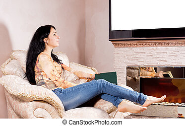 Woman daydreaming in front of the fire