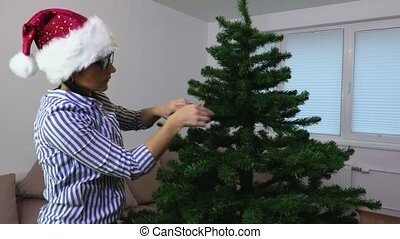Woman decorate artificial Christmas tree