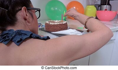 Woman decorate cake with candles on the table in kitchen