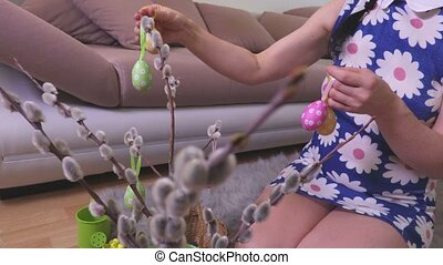 Woman decorate pussy willow with Easter eggs