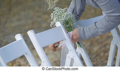 woman decorated chairs for the wedding ceremony.
