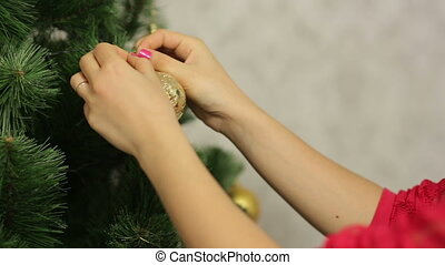 Woman decorates christmass tree