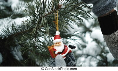Woman decorates fir-tree with toy during new year in forest....