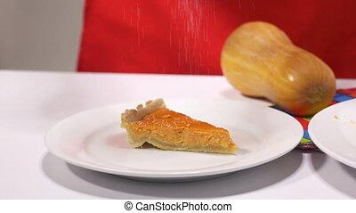 Woman decorates piece of a pumpkin pie with powdered sugar -...