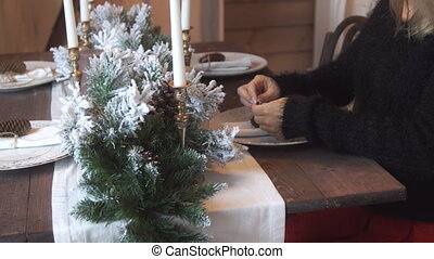 Woman decorates the Christmas table