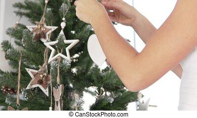 Woman decorates the Christmas tree.