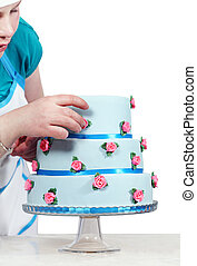 Woman decorates three-story blue cake, isolated on a white ...