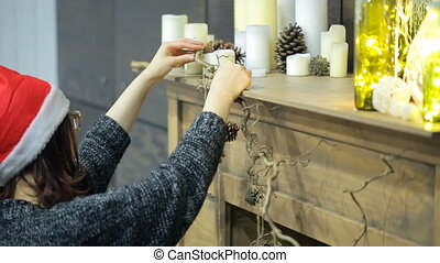 Woman decorates wooden fireplace to celebrate Christmas, New Year.
