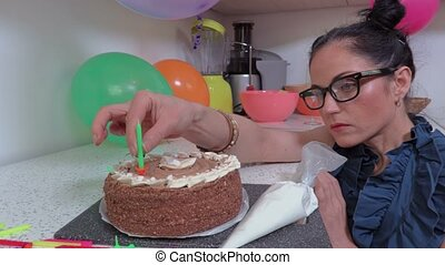 Woman decorating birthday cake with candles