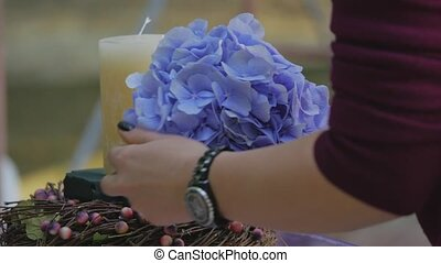 woman decorating candles with flowers for wedding