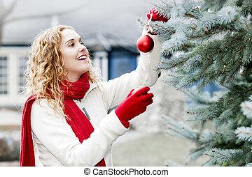 Woman decorating Christmas tree outside
