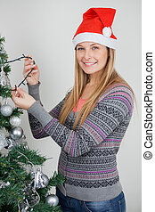 Woman Decorating Christmas Tree With Fairy Lights