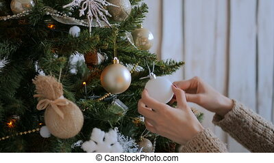 Woman decorating christmas tree with toys. Holidays, x-mas...