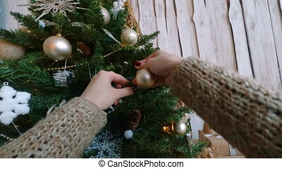 Woman decorating christmas tree with toys