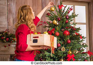 Woman decorating christmas tree