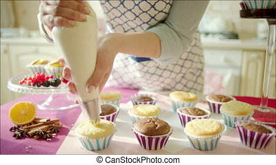 Woman decorating cup-cakes - Shot of woman's hands putting...