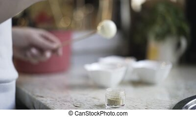 Woman decorating homemade candy with a brush