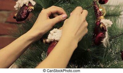 woman decorating on Christmas tree with Christmas toys.