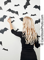 Woman decorating room for Halloween celebration