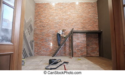 Woman decorator stands the stairs staining her steps. Blonde...