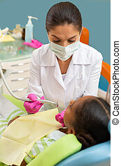 Woman dentist leaning over a young female patient