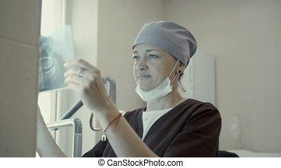 Woman dentist looks rentgent jaw 4K