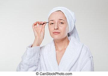 Woman depilating her eyebrow