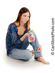 Woman depressed siting on the flor with flowers in hand