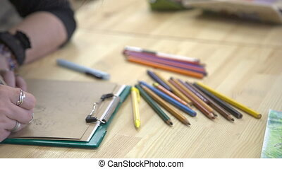 Woman designer think over layout of cards with a greeting on table with lots of crayons.