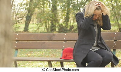 broken heart woman crying sitting on a bench on a autumn day, she is depressed and fells abandoned steady cam